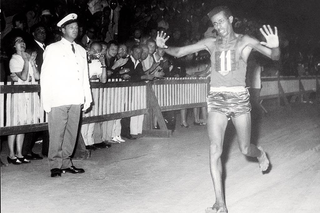 """Abebe Bikila che a piedi nudi si avvia solitario verso la vittoria (con record olimpico in 2h15'16"""") della maratona (42,195 km)."""
