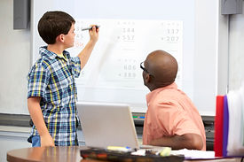 Boy age 10 with tutor doing sums on whit
