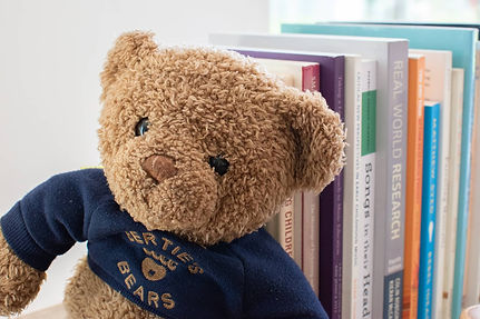 Teddy bear propped up against music research books