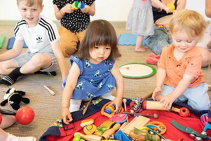 Little girl in blue dress choosing an instrument to play in Little Bees class.