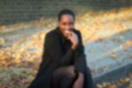 Dr Samara Linton: grinning in a black coat on a pavement covered in autumn leaves