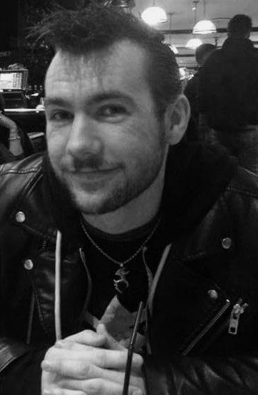 Black and white portrait of Lex Jones wearing a leather jacket. He has a short beard and dark hair standing up in a quiff