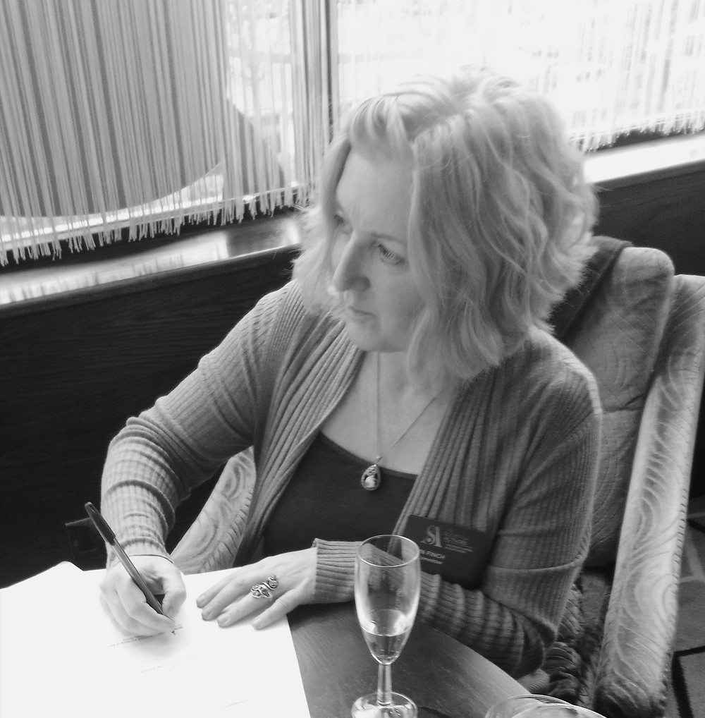 Black and white image of author Dawn French signing her contract with Stirling Publishing