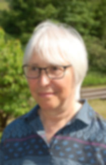 Portrait of Sylvia Hehir, a lady with white hair, brown eyes, and black-rimmed glasses. She smiles slightly in front of a greenery, wearing a patterned blue shirt