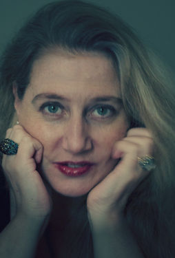 Potrait of Tabatha Stirling: long blonde hair and red lipstick, her face resting on her hands that have large rings