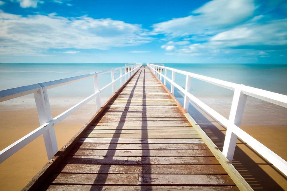 мостик в море с голубыми облаками и пляжем