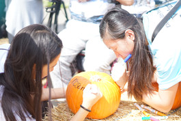 Event attendees design attendees designing a pumpkin as part of the disablity pride event