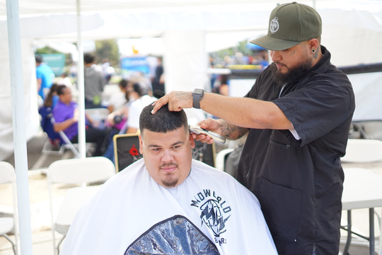 event atrtendee getting hair cut at one of the event booths.
