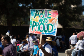 """image of a disabled individual holding a sign that reads """"able and proud"""""""