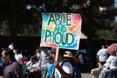 """Prade attendee holding a sign that reads """"able and proud"""""""