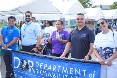 Parade attendees from the Department of Rehabilitation holding their organizations banner
