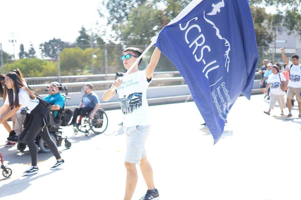 event attendee walking along the parade route while holding a flag representing the SCRS logo