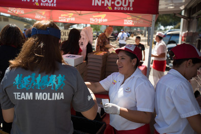 in-n-out workers serving food to parade attendies