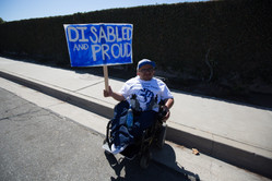 """SCRS Director of Public Policy holding a sign that reads """"disabled and proud"""""""