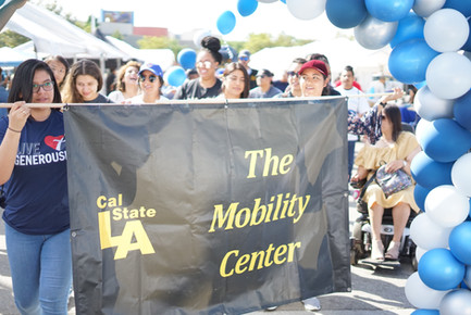 """prade attendees holding a banner representing their organisation that reads """"Cal State LA, The Mobility Center"""""""