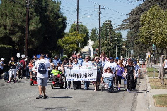 prade attendees holding a banner with the pride parade logo