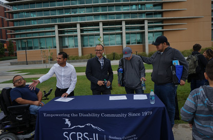 picture of scrs staff standing behind table at laptop giveaway event