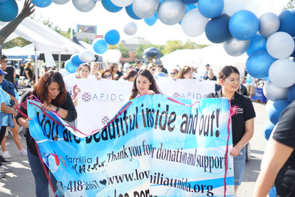 """prade attendees holding a banner representing their organisation that reads """"beautiful insde and out"""""""
