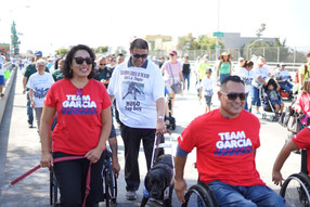 event attendees walking along the parade route alongside a wheelchair user