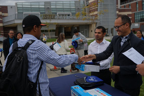 picture of college staff shaking hands with students