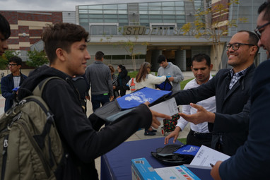 picture 2 of college staff handing  students a laptop during the givaway