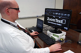 """Image of an individual using a computer with the words """"zoom text"""" on the screen"""