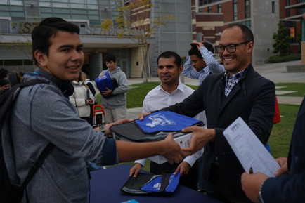 picture of college staff handing  students a laptop during the givaway