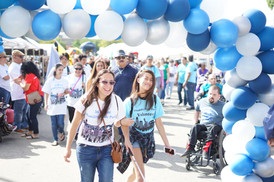 Parade attendees walking through an archway made of baloons in the event colors