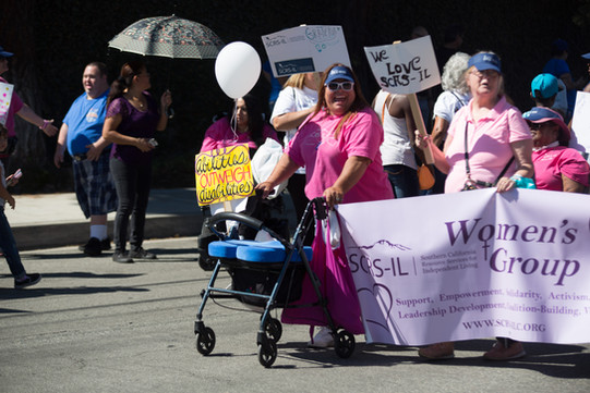 """group of SCRS womens group attendees walking along the parade route holding a banner that reads """"womens group"""""""