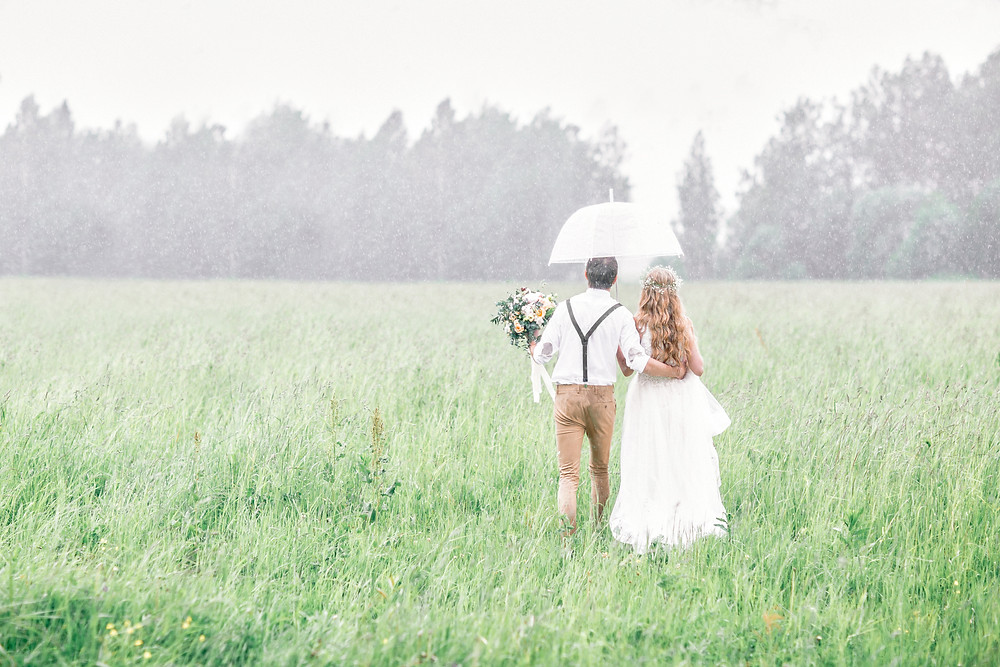 bride and groom walking in the rain under an umbrella in a field