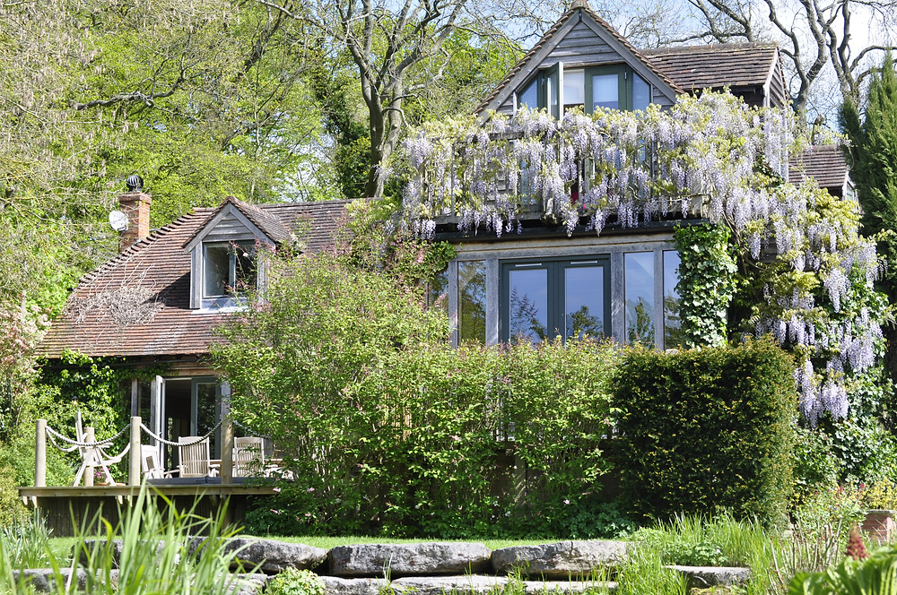 wisteria covered balcony across oak framed house