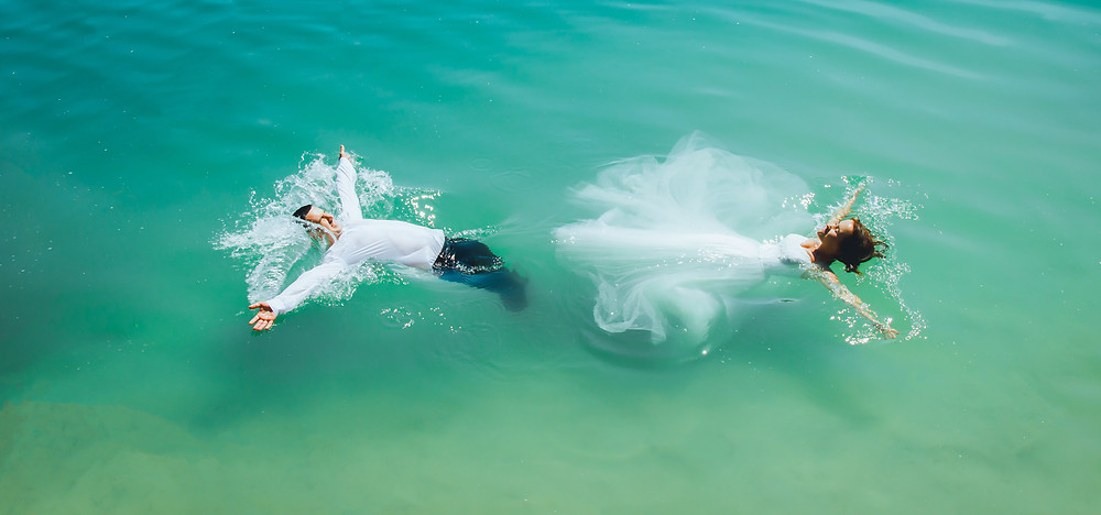 Bride and groom swimming in the sea wearing their clothes