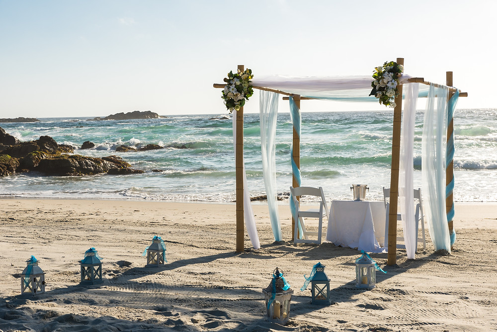candles and drapes laid out on a beach for a wedding ceremony