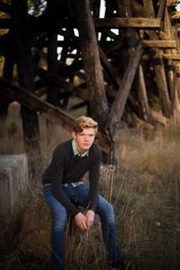 Senior boy photo at railroad bridge in Rainier, WA