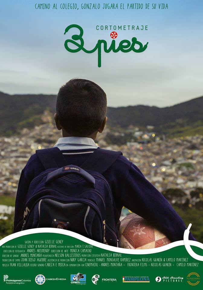 We see a young boy from the back, holding a football under his arm, as he looks out over his home town below.
