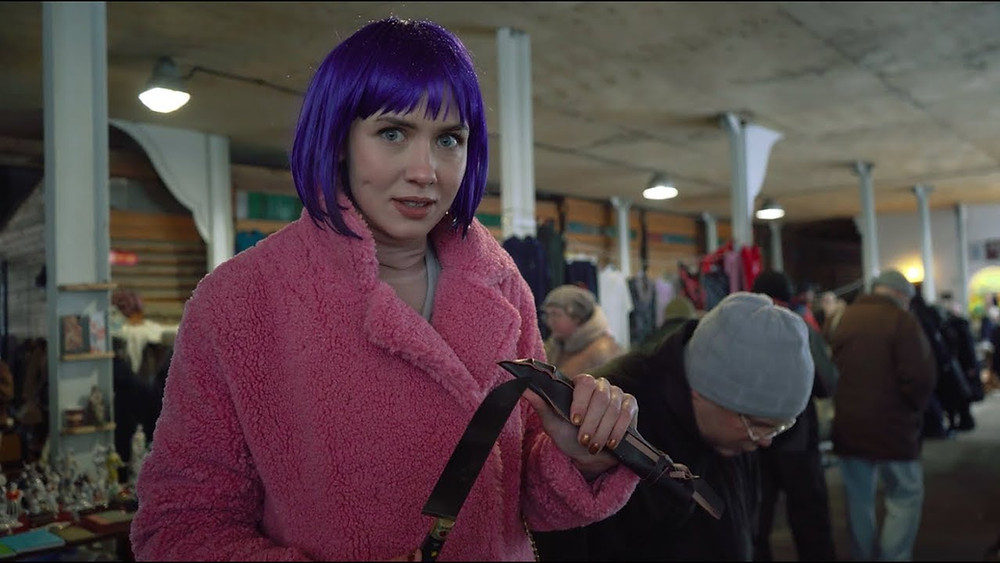 A young Russian woman in pink fur and purple wig holds a large knife and shows it to the camera.