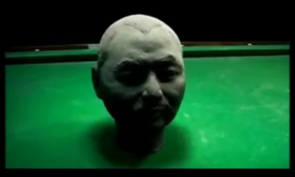 A clay sculpture of a man's head sits in the middle of a pool table.