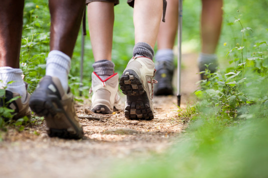 shoes-of-people-trekking-in-wood-and-wal
