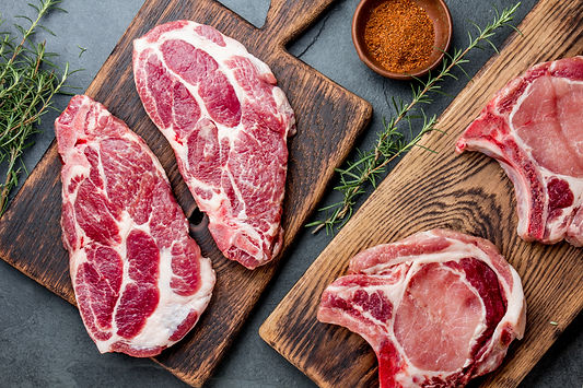 raw-pork-steaks-with-seasoning-on-wooden
