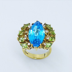 Ring in 18kt gold with Blue Topaz, Peridots and brilliant diamonds