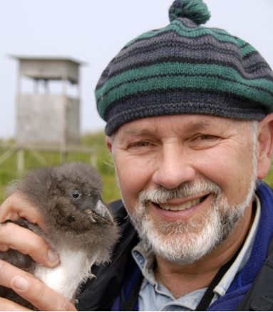 Dr. Stephen Kress wearing a knit cap smiles at the camerawhile holding a baby bird.