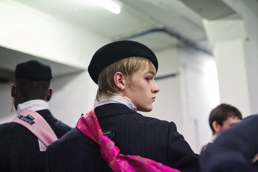 """South Korea's Münn returned to the UK runway at London Fashion Week Mens for Autumn Winter 20. With echoes of Dandy Highwaymen, Baroque Baronets and an altogether air of suave sophistication, this was a lesson in repackaging """"Englishness"""" and delivering it back to the Brits.  Super 120's woollen suiting fabric from Huddersfield mills, birthplace of the finest Saville Row cloths was paired with artisan Japanese denim and Harris Tweed to produce a forward thinking collection abundant in historical references, elegance and charm.  Designer Hyun-Min Han's new vision of The English Gentleman drew on the hunting, fishing and shooting styles so beloved of country landowners but clashed this with high neck shirting and scarves reminiscent of Victorian dandies. Extra swagger and attitude came in the form of Adam & The Ants-esque printed and embroidered trousers and city boy chic pinstripes.  Berets, feathers and plumes adorned the heads of models whist the humble neck tie, so rarely seen in contemporary directional fashion, was styled loose, regular and as an adornment to a cape-style reworking of the classic English trench coat.  Sheer fabrics were draped and layered revealing labelling worn on the outside - a detail prevalent through the entire collection. Exposed tailors basting stitches and makers mark selvedges were also prevalent throughout. A firm acknowledgement of the fine craftsmanship of fabrics assembled for the collection.   Münn have deconstructed what constitutes 'The British Look' and re-assembled the constituent parts to present a collection with all the confidence and contemporary dynamics of a brand that is poised to break out of Asia and hit Europe hard."""