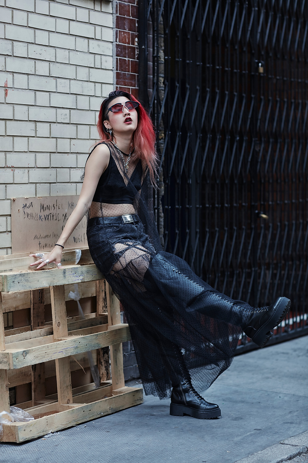 young Thai female with flame red hair leans back in a London side street against a tiled wall and wooden pallet wearing knee high Dr Martens style boots, cut off black denim shorts, a sports bra style top and a sheer black dress overlay