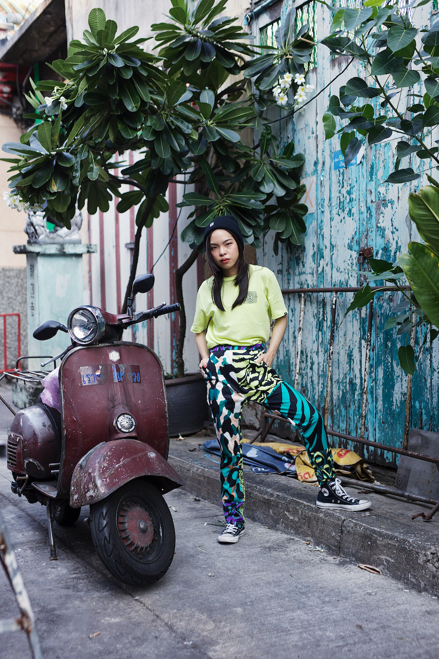Pear is a 22 year old female fashion & design student at Bangkok's Silpakorn University Decorative Arts department. This photo shows pear dresses in a contemporary slouchy street wear style with 80's and 90's skateboarder influences. She is wearing blue and aqua multi pattern loose trousers and a lime green t shirt with a skateboard style logo along with Converse Chuck Taylor baseball boots. Pear is pictured next to a rusting old motor scooter and large wooden door with peeling blue paint creating a beautiful patina. The image is framed nicely with large exotic trees growing from earthenware pots outside an old temple in bankbook's Chinatown