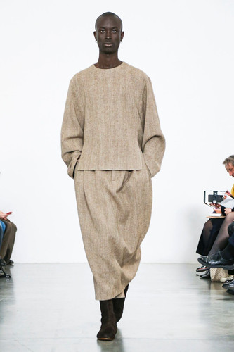 "HED MAYNER - Autumn Winter 2020   Simplicity, wearability and the re-working of traditional design classic are at the forefront of the Hed Mayner design aesthetic.   The 2019 recipient of the LVMH Karl Lagerfeld prize (formerly known as the ""special prize""), Mayner focuses on an everyday wardrobe with minimal neutral tones as key. From sand, grey and nude, Mayner flirts with a neo-military aesthetic lime greens and blues with wide coloured striping across two looks.    Using oversized knit in cocoon effect, buttonless cardigan and body wraps are juxtaposed with super relaxed oversized suiting - often worn with roll necked tops. An undying commitment to the reworking of classic lines for a relaxed yet luxurious take on tailoring and formality is at the heart of Hed Mayner's AW20 collection.    Emphasising comfort and self-expression, there is freedom within the garments for the wearer to adapt to their own lifestyle and tastes."