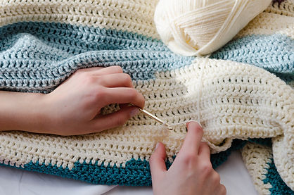 Hands using a crochet hook on a blue and white blanket
