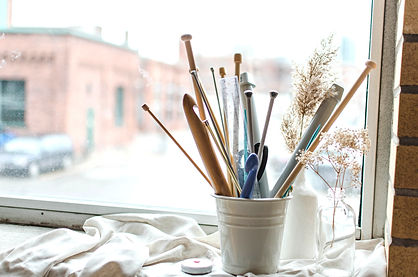 A window sill with a bucket of knitting and crochet tools