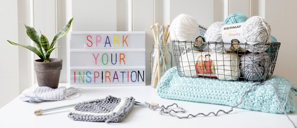 Board saying Spark your inspiration and yarn on a desk