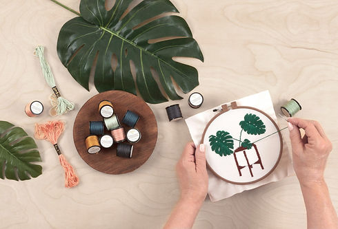 A person's hands embroidering a plant on a hoop