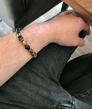 bras d'hommes représentant un bracelet œil de tigre poser sur la jambe